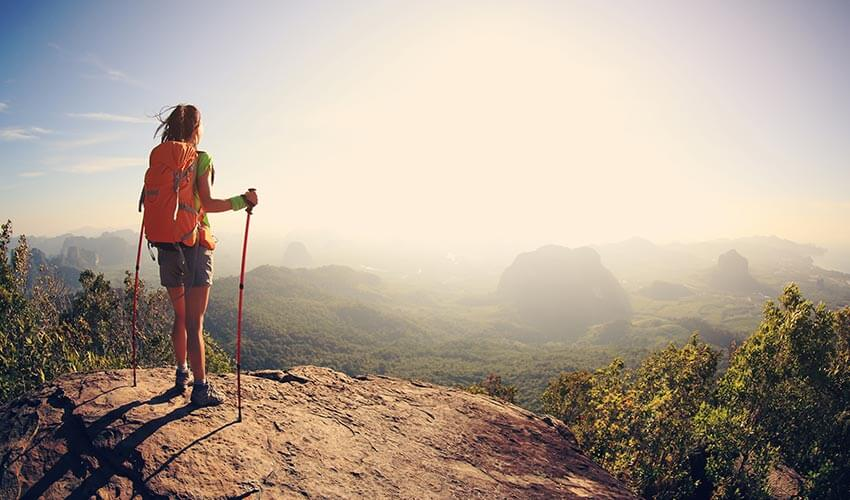 young woman backpacker hiking at seaside mountain cliff