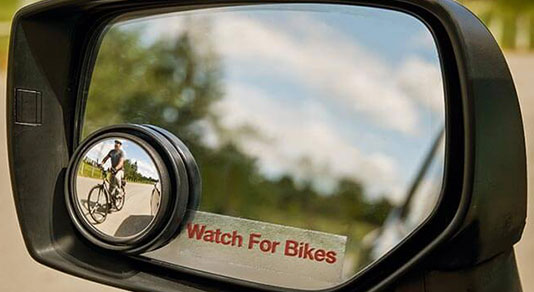 A side mirror with the CAA Watch for Bikes decal