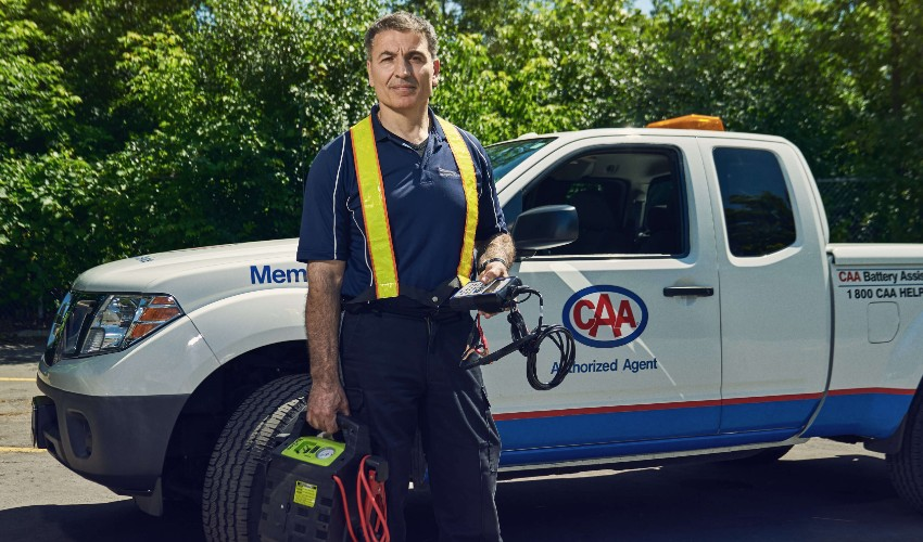 CAA Battery Technician with testing kit standing in front of CAA service vehicle.