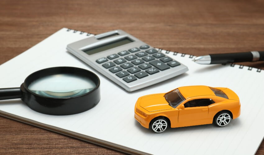 Yellow toy car, magnifying glass, calculator, pen and notebook sitting on wooden desk.