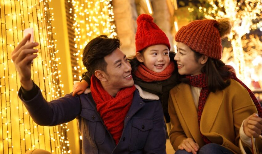 Parents taking a photo with their young daughter at an outdoor holiday event.