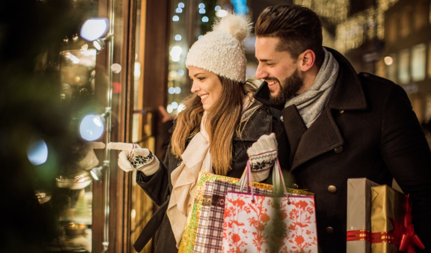 Young couple holding holiday shopping bags and looking at shop displays outdoors.