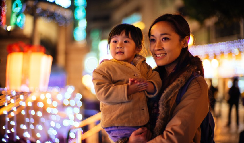 Mom and young daughter enjoying holiday lights outdoors.