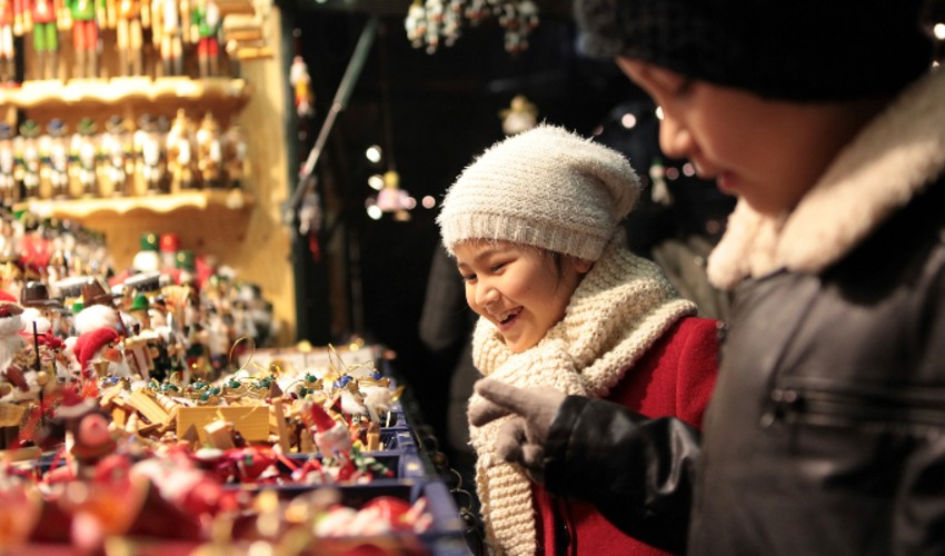 Young boy and girl looking for decorations at a Christmas market.