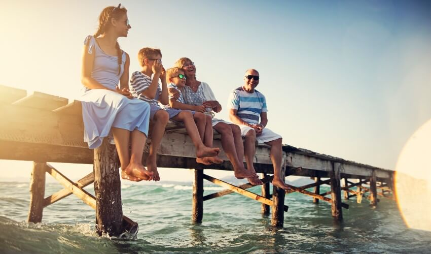 Family sitting on pier by the sea.