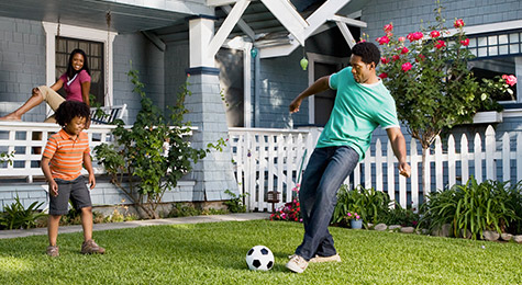 Two kids playing soccer in front yard.