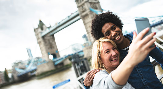 Ethnic travelers taking a selfie with London Bridge in background.